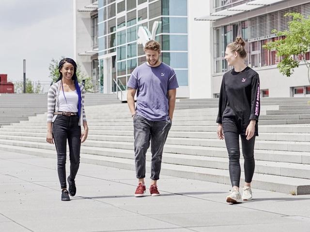 drei Mitarbeiter vor dem PUMA Gebäude