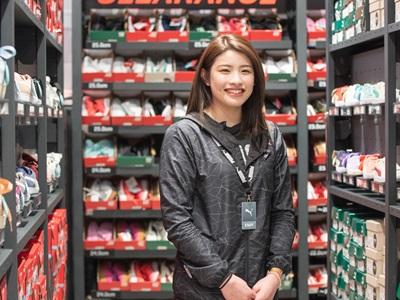 Lächelnde PUMA Mitarbeiterin im Store