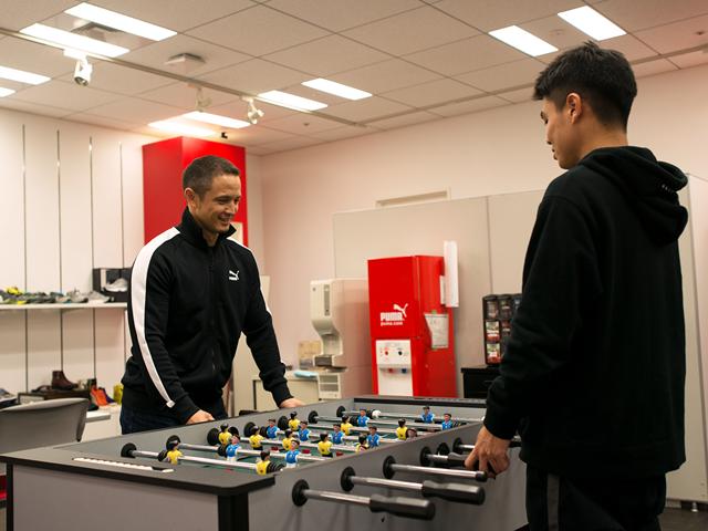 Zwei PUMA Mitarbeiter spielen Tischkicker