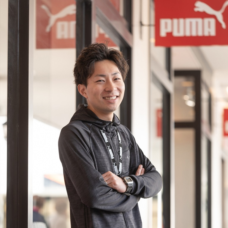 Lachender PUMA Mitarbeiter vor dem PUMA Store