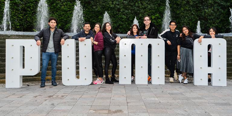 Lächelnde PUMA Mitarbeiter stehen zwischen den Buchstaben des PUMA Logos