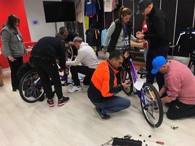 PUMA Mitarbeiter bauen Fahrräder für Kinder