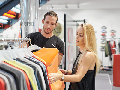 Two employees looking at PUMA clothing